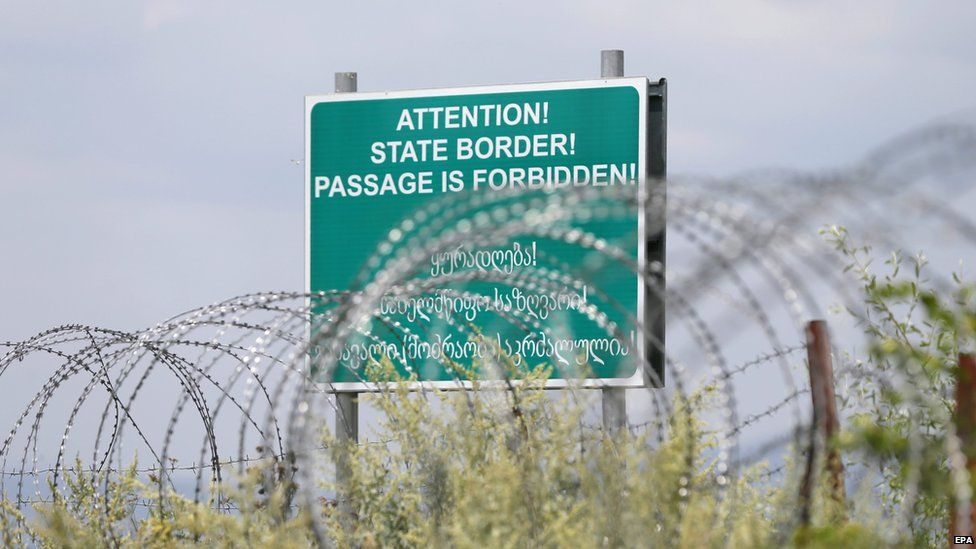 A warning sign is pictured behind a barbed wire barricade erected by Russian and Ossetian troops along Georgia's de-facto border with its breakaway region of South Ossetia, 14 July 2015