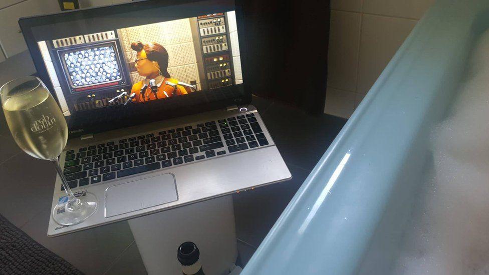 Роуэн Брюс смотрит фильм и пьет вино в ванне