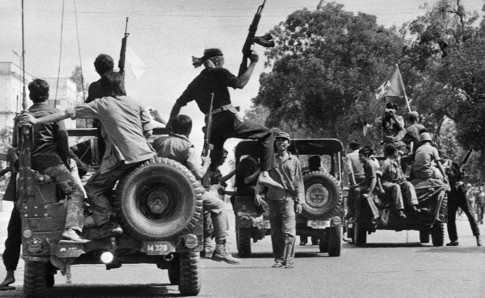 The Khmer Rouge guerilla soldiers wearing black uniforms (C), drive 17 April 1975 atop jeeps