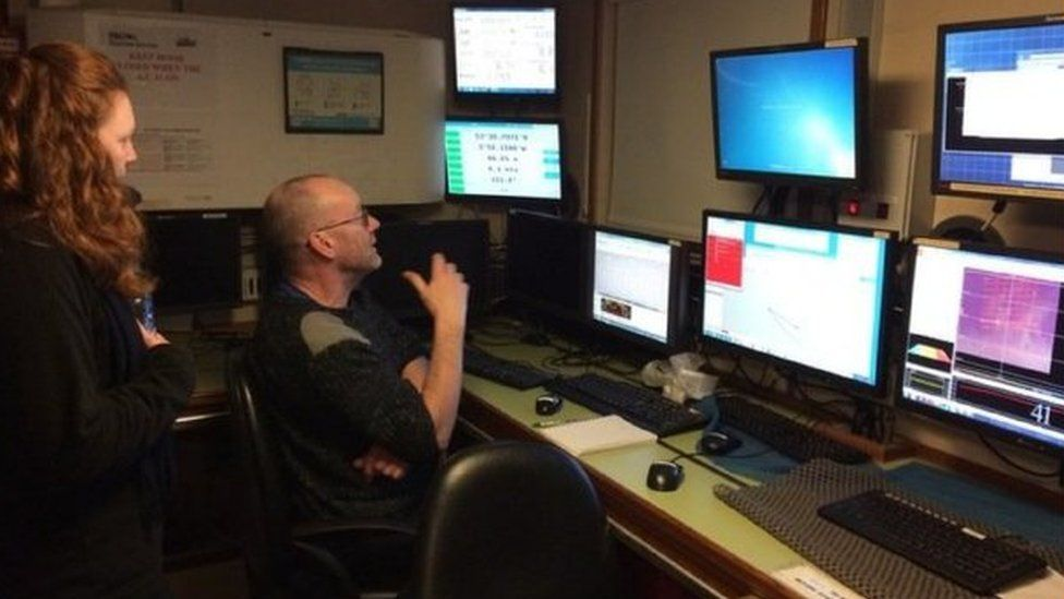 Boat crew monitor a bank of screens
