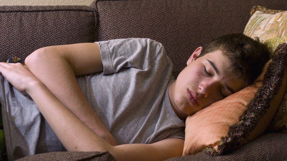 Teenage boy asleep on sofa