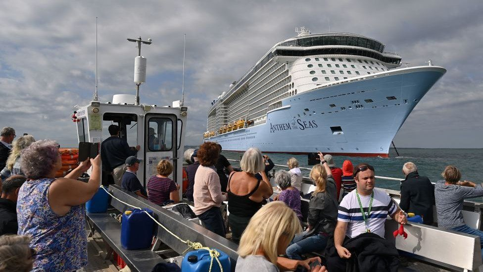 small boat of sight-seekers looking at big cruise ship