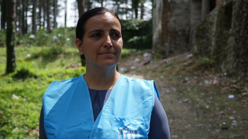 Francesca Bonelli from UNHCR stands near some trees in a green space
