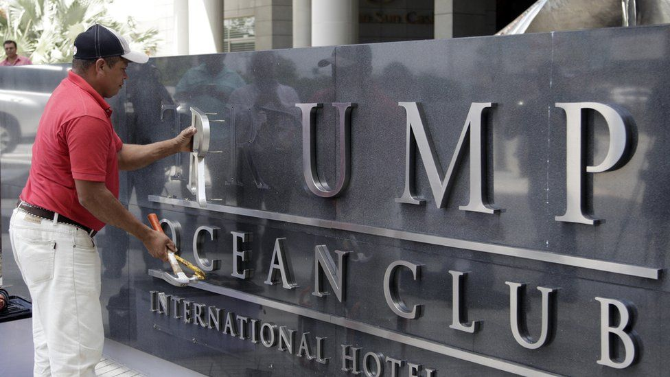 A worker removes the Trump sign letters from outside the hotel in Panama City on March 5, 2018