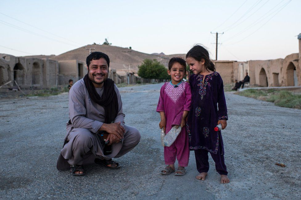 Aliyas Dayee with local kids on the main road of the largely abandoned Tangay Bazaar, in government-controlled Kajaki.