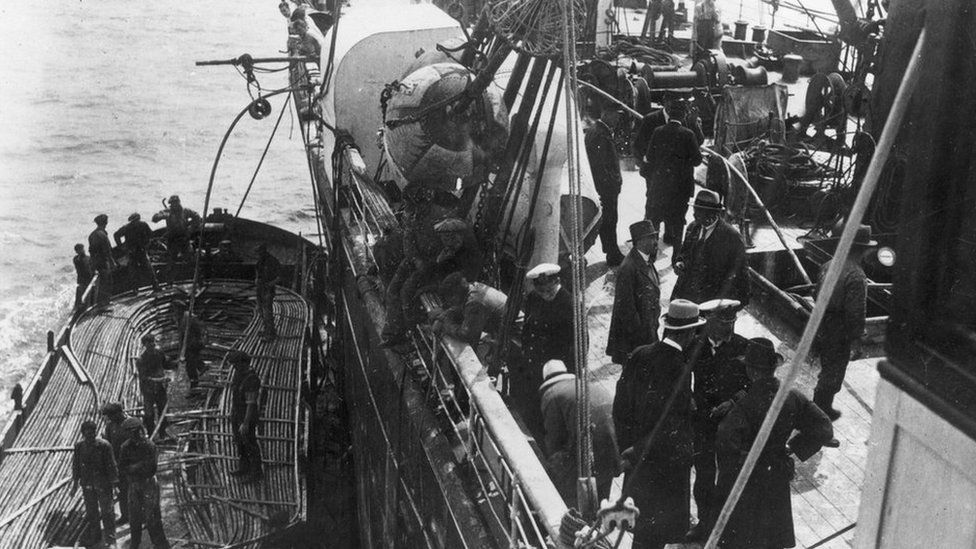 Groups of men on the deck of a ship which laying telegraph cable at sea, with the image showing men looking over the side of the ship at a smaller vessel carrying the cable, circa 1900