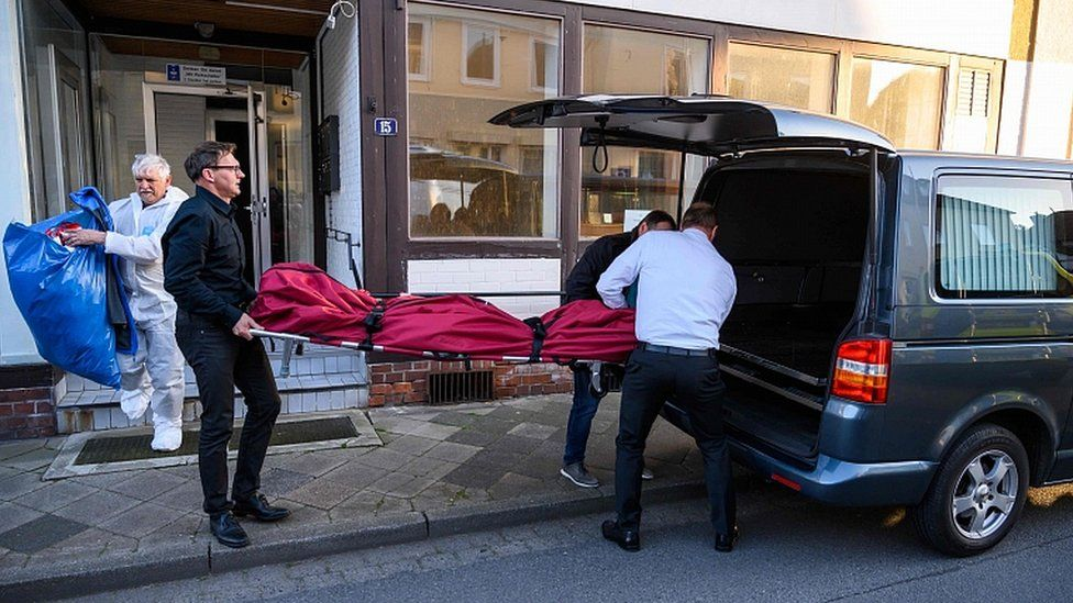 Undertakers carry a body on May 13, 2019 out of a house in Wittingen, northern Germany
