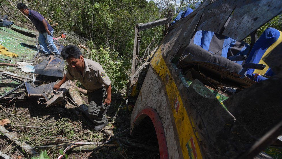 Neighbours and first responders inspect the area of a bus accident near Yolosita