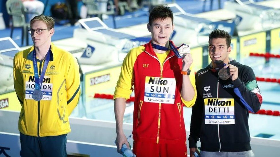 Mack Horton stands in the background as Sun Yang and Gabriele Detti pose for photos with their medals