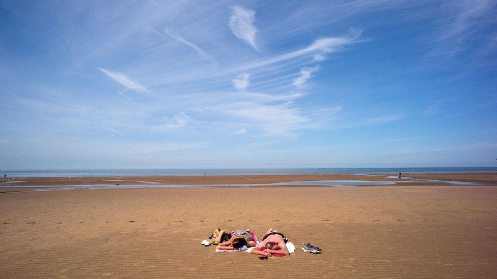 Holidaymakers enjoy the high temperatures on Blackpool beach on 19 June 2017