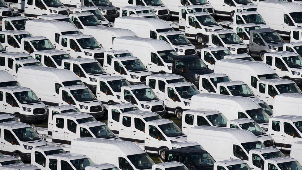 A photograph shows hundreds of white vans parked in neat lines queuing in a port. There are two non-white vans visible - one black and one grey