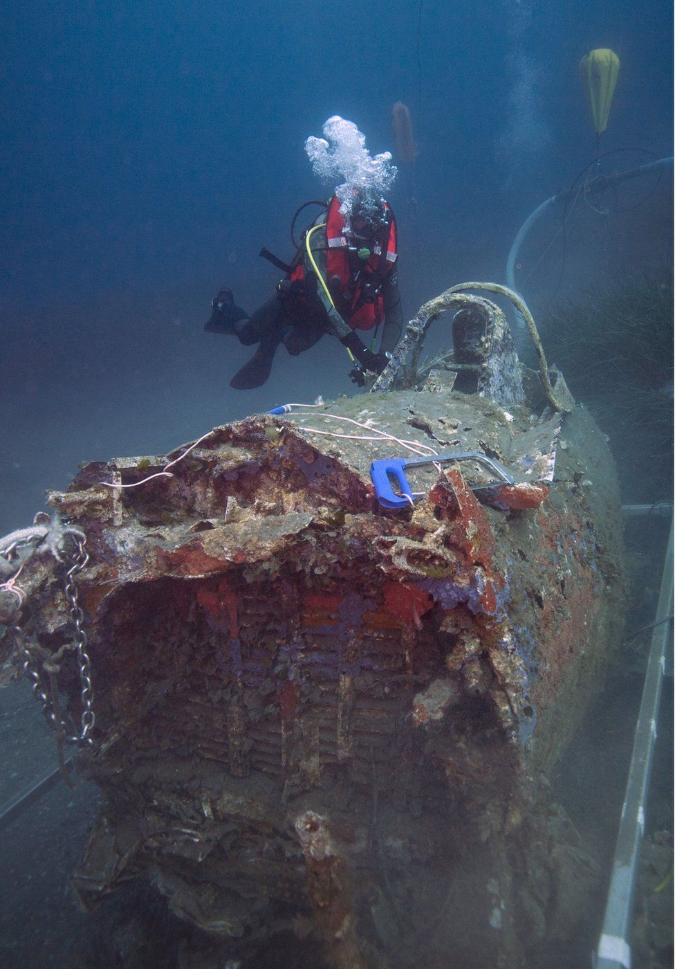 A French military diver member of the FS Pluton M622 navy de-mining ship, swims on July 2, 2018, above the wreck of an USAAF P-47 Thunderbolt (Warthog) US fighter plane