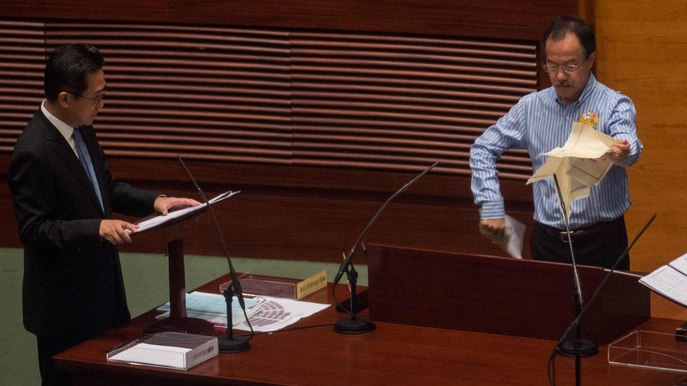 """Newly elected lawmaker Fernando Cheung (R) tears a mock """"831 ruling"""" as he stands to take the Legislative Council Oath"""