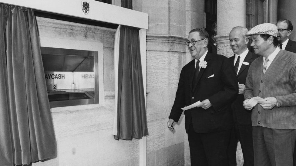 Sir Thomas Bland unveils the first Barclaycash machine alongside TV actor Reg Varney, in Enfield, north London