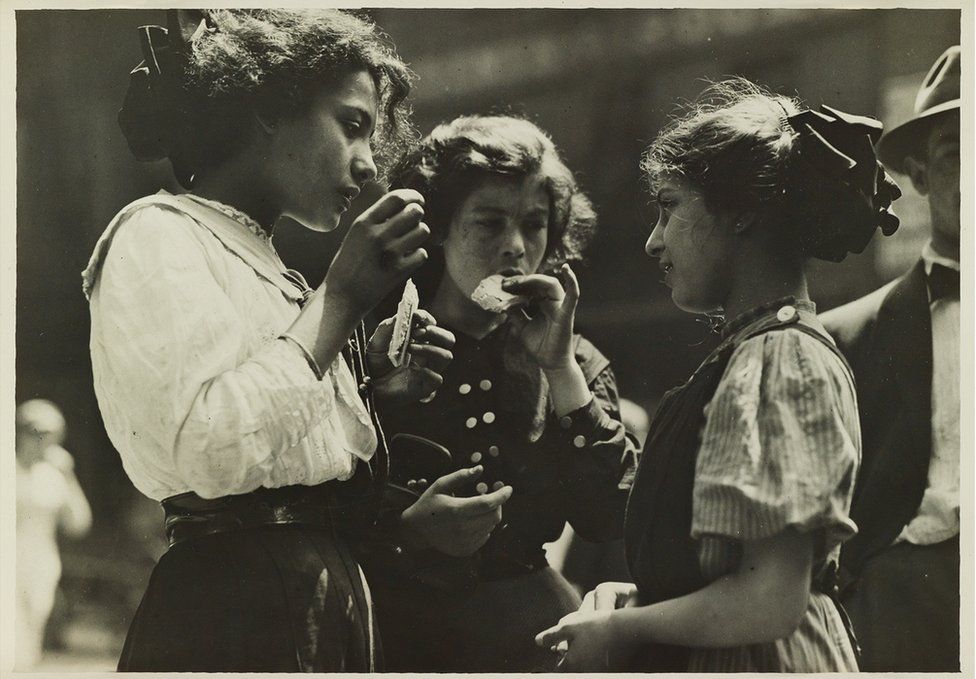 A group of three children eating.
