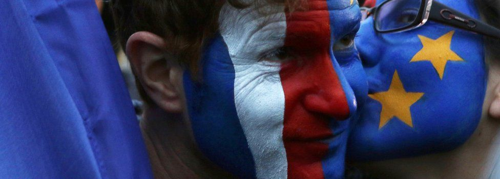 Supporters of French president-elect Emmanuel Macron painted with the French and EU flags celebrate at the Louvre Museum in Paris on 7 May 2017, after the second round of the French presidential election