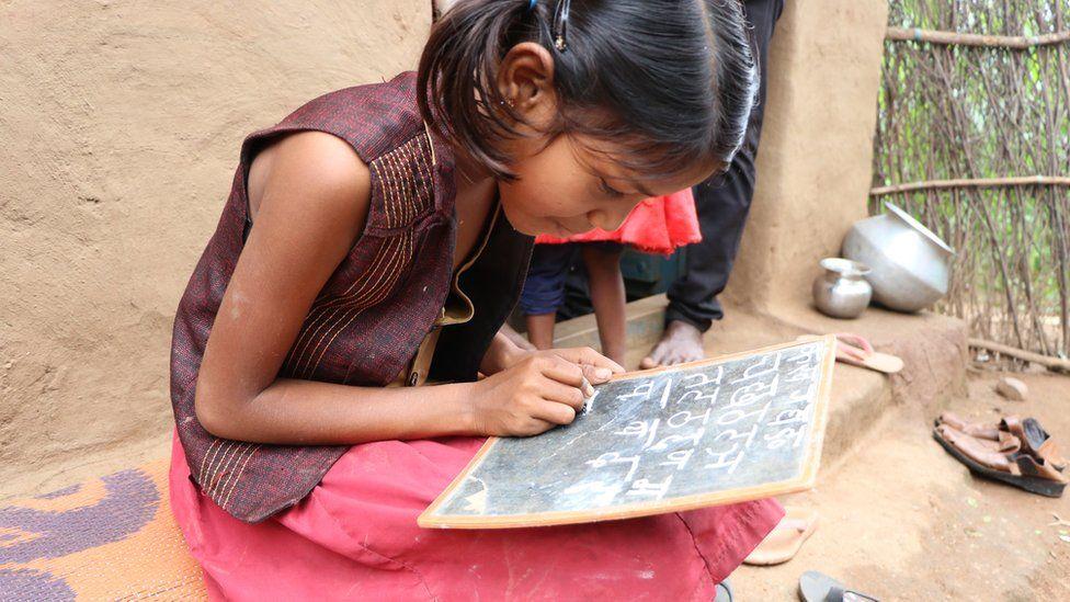 Radhika writing the Hindi alphabet on a slate.
