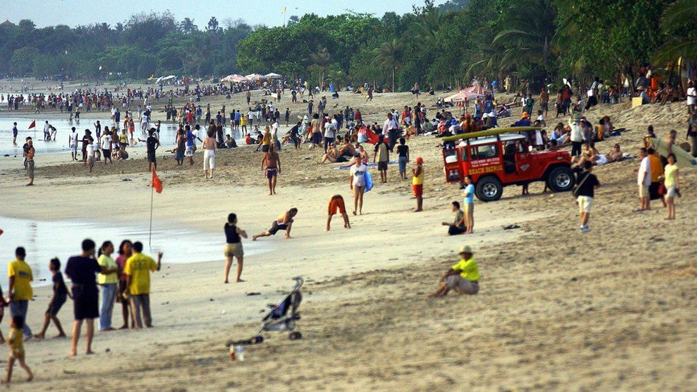 Foreign and local tourists enjoy their evening along a beach in Kuta, on Bali island, 2 October 2005