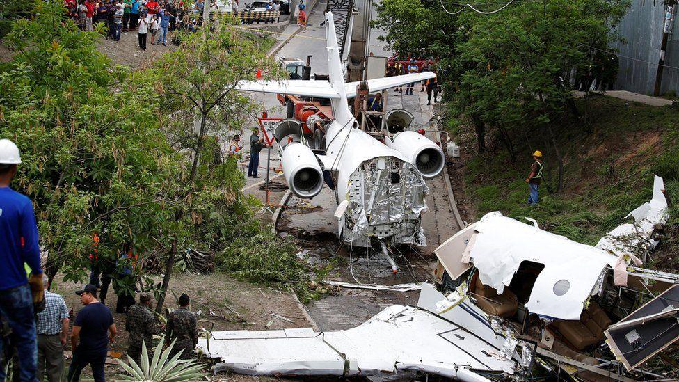 A crane lifts the wreckage of a Gulfstream G200 aircraft that skidded off the runway during landing at Toncontin International Airport in Tegucigalpa, Honduras