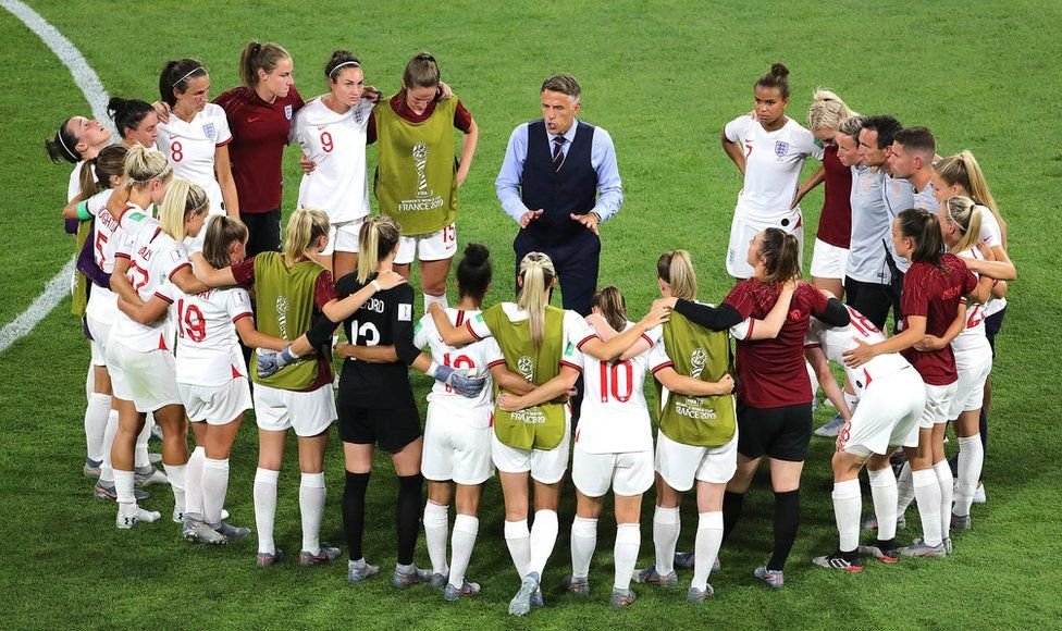 England head coach Phil Neville talks to the players after the final whistle of the semi-final