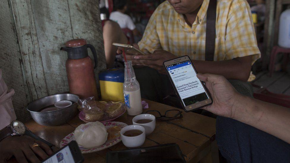 People look at Facebook on their phones at a teashop in Yangon, Myanmar, in August 2018