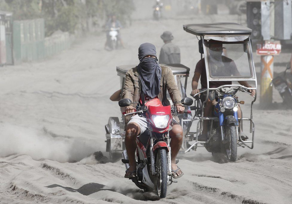 People travel along a road covered in ash deposits, a day after the eruption of Taal Volcano, in Agoncillo town in Batangas province, Philippines, 13 January 2020