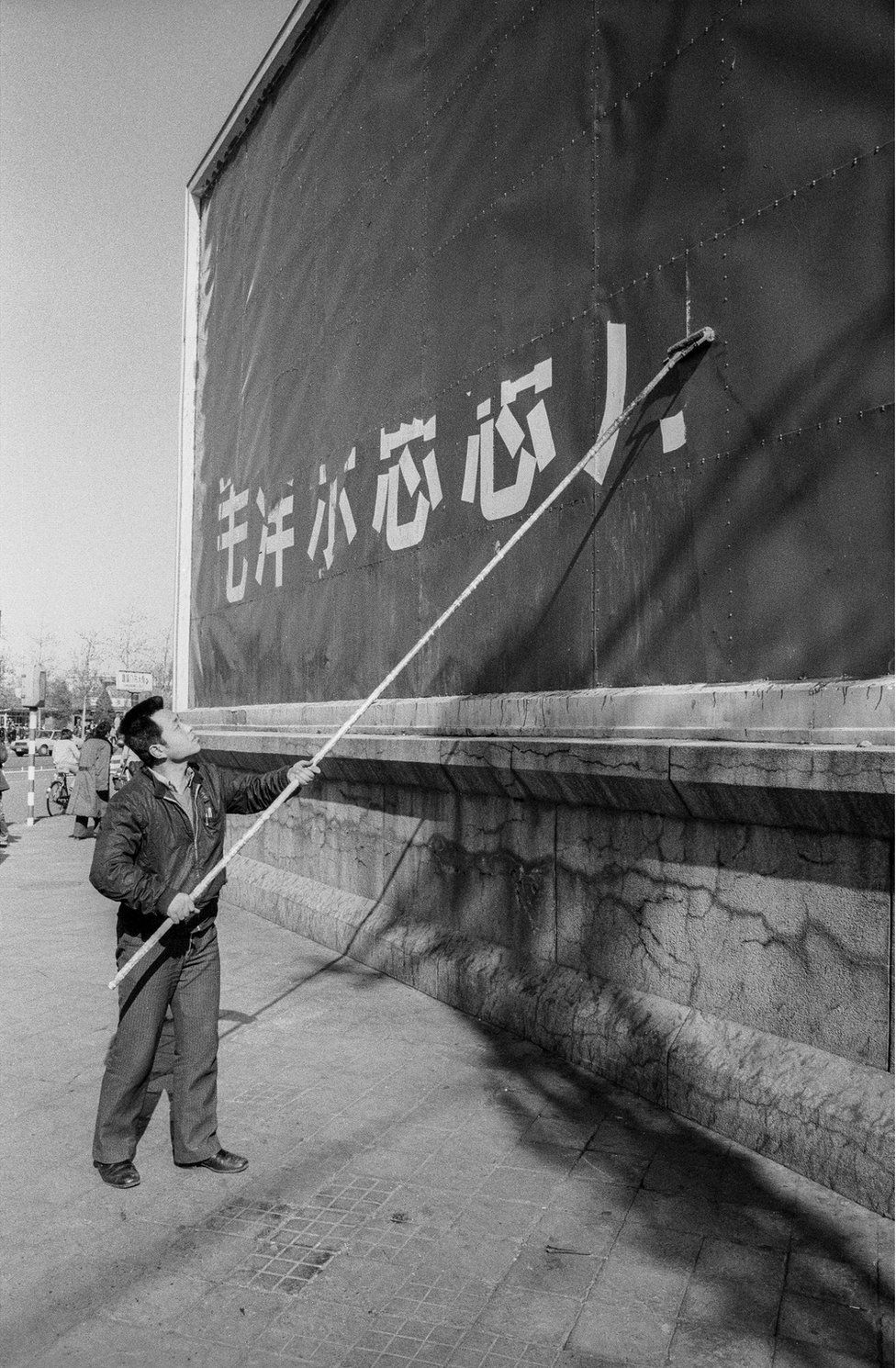 A man paints over a billboard
