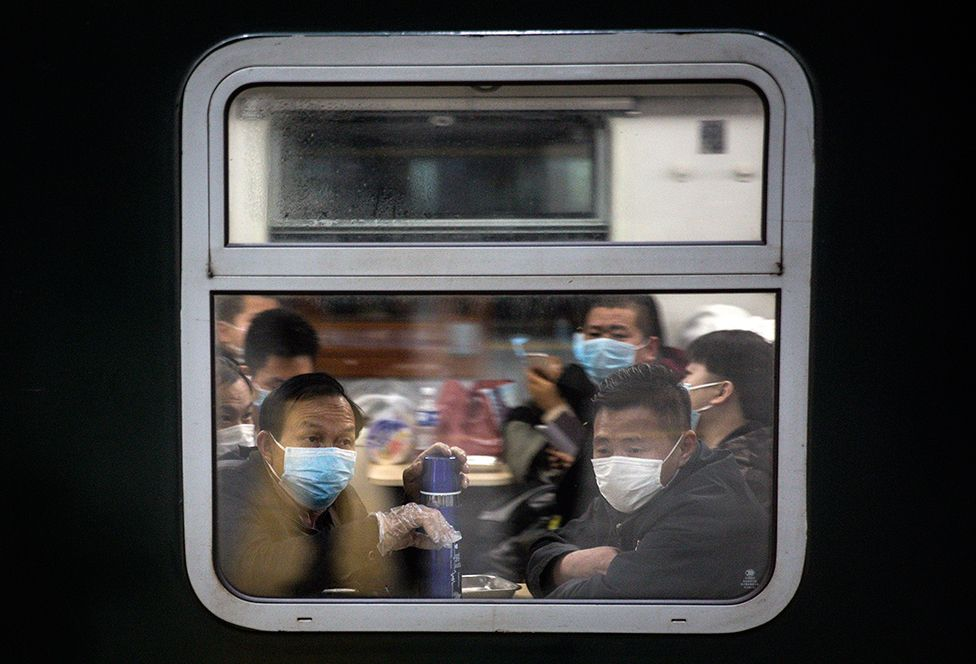 Passengers sit in a train carriage looking out the window
