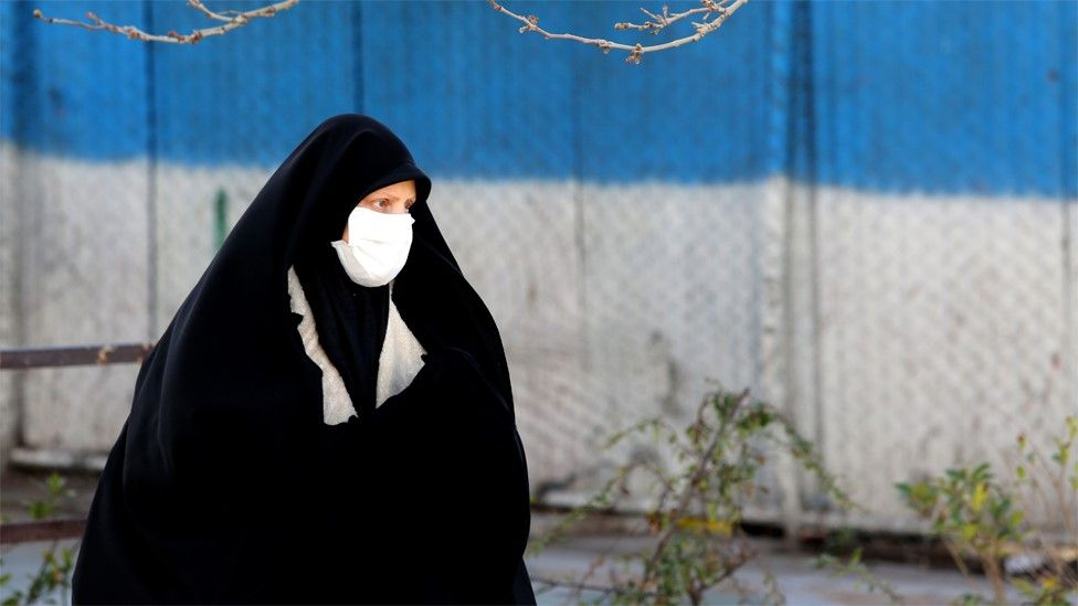 A woman wearing a face mask walks down a street in Tehran (2 March 2020)