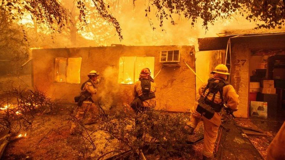 Firefighters tackle a fire in Paradise, California.