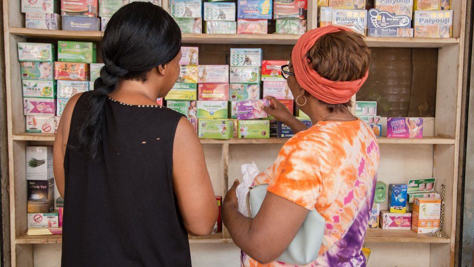 Two women looking at shelves of medicine