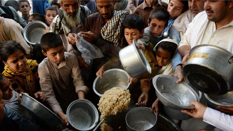 Afghan children hold dishes as they wait to receive food donated by a private charity for the needy during the Islamic holy month of Ramadan in the city of Jalalabad on 9 June 2016