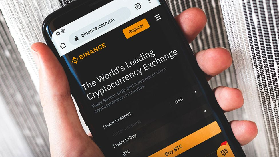 Binance cryptocurrency exchange website interface on a smartphone held in hand