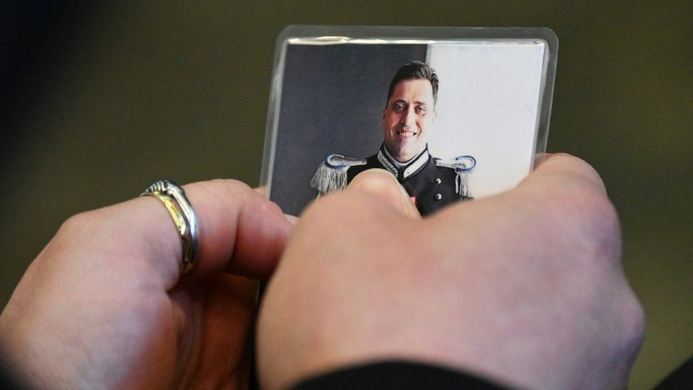 The police officer's widow holds a photo of her late husband in court