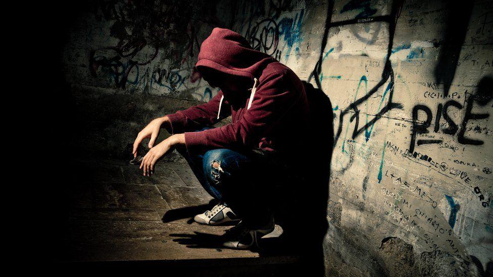 Anonymous teenager in dark corner