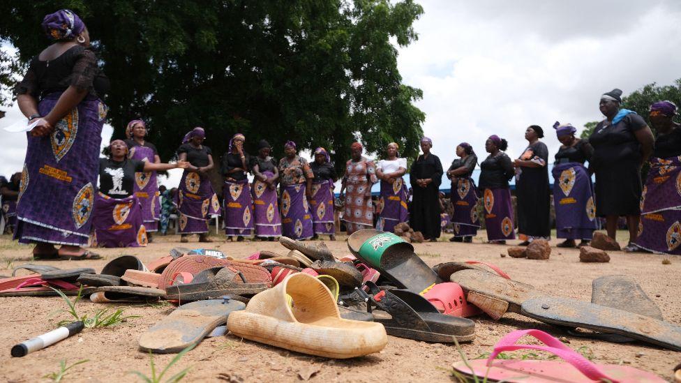 Les parents d'élèves kidnappés du lycée Bethel Baptist, dans l'État de Kaduna au Nigeria, se tiennent à côté des chaussures laissées après l'attaque - juillet 2021