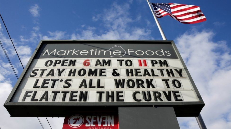 """A market marquee in Seattle, Washington reads """"stay home and healthy, let's all work to flatten the curve"""""""