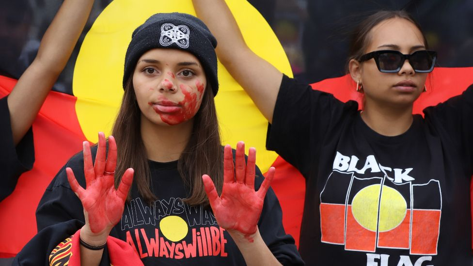 Protesters with red paint on their hands at a rally against black deaths in custody