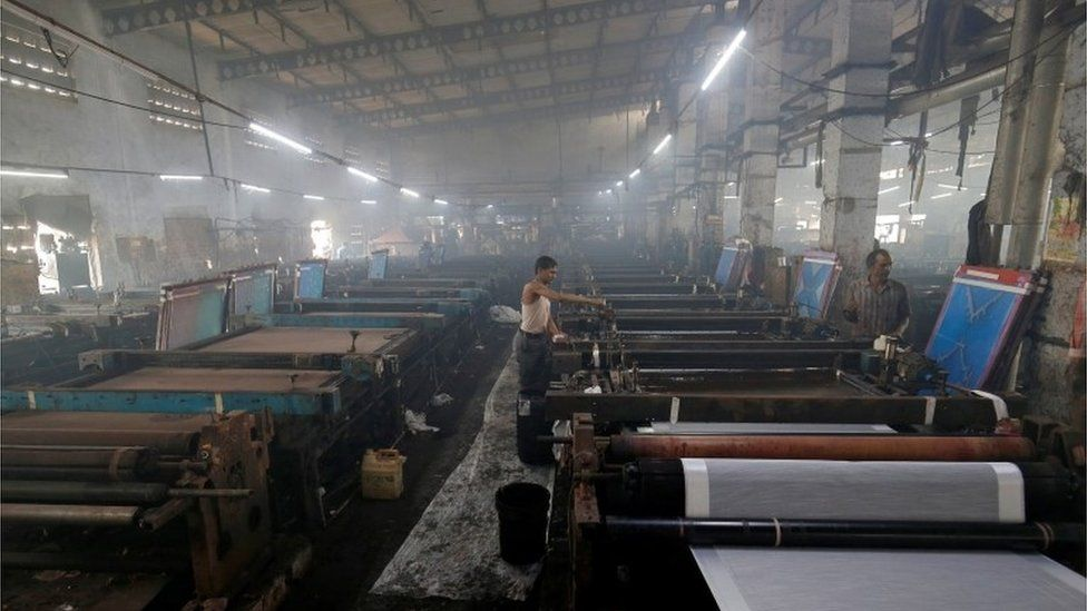 Employees work inside a sari, a traditional clothing worn by women, manufacturing factory in Surat, India, March 8, 2019