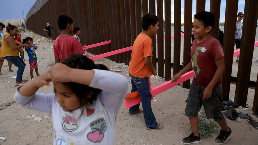 Children play on seesaws at the Mexican border