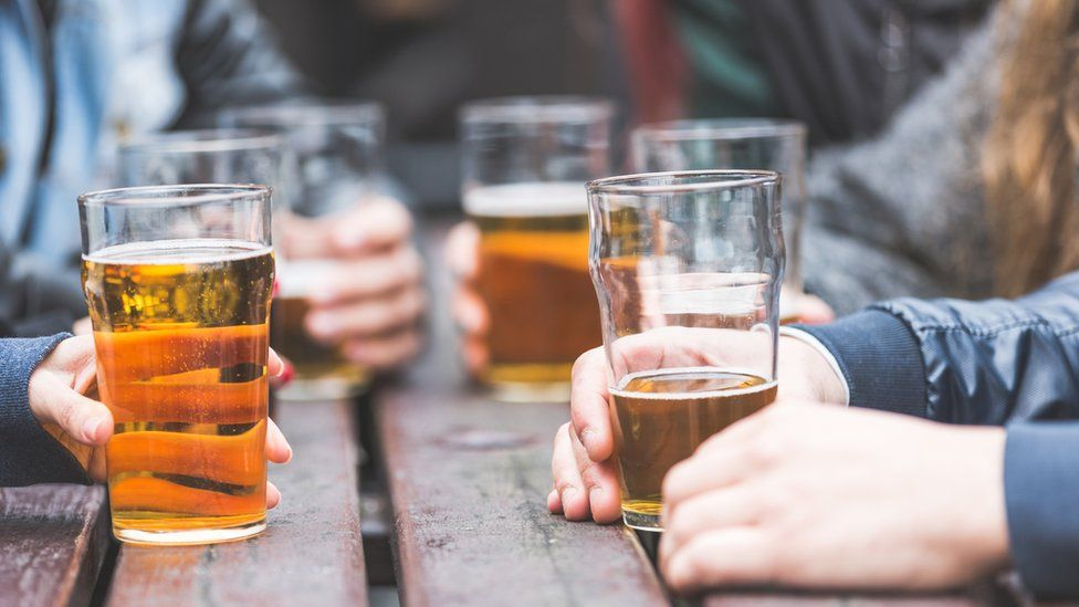 Hands holding beer glasses