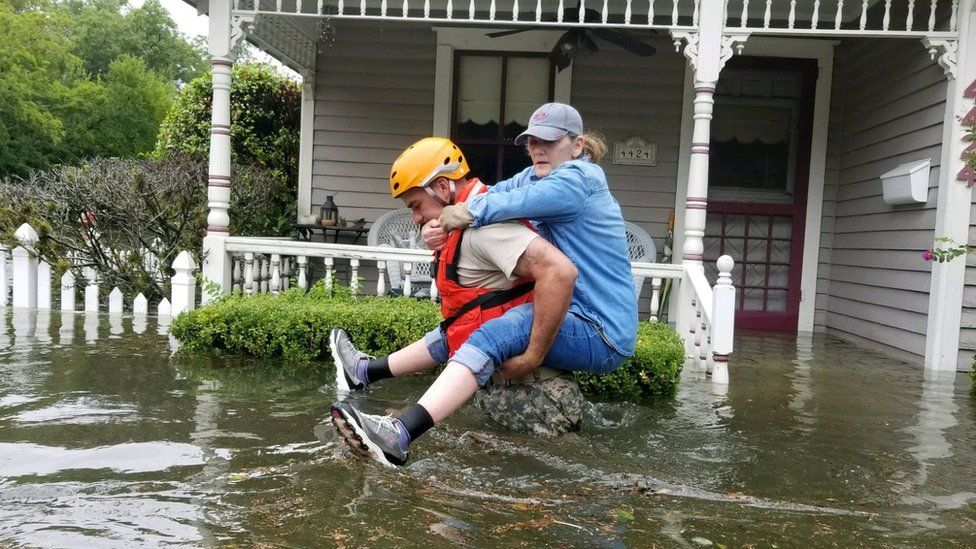 A Texas National Guard soldier carries a woman on his bank as they conduct rescue operations in flooded areas around Houston, Texas, U.S., August 27, 201