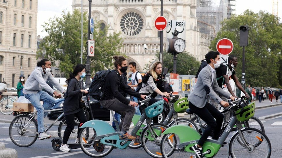 Bikers wearing protective masks ride past Notre Dame Cathedral