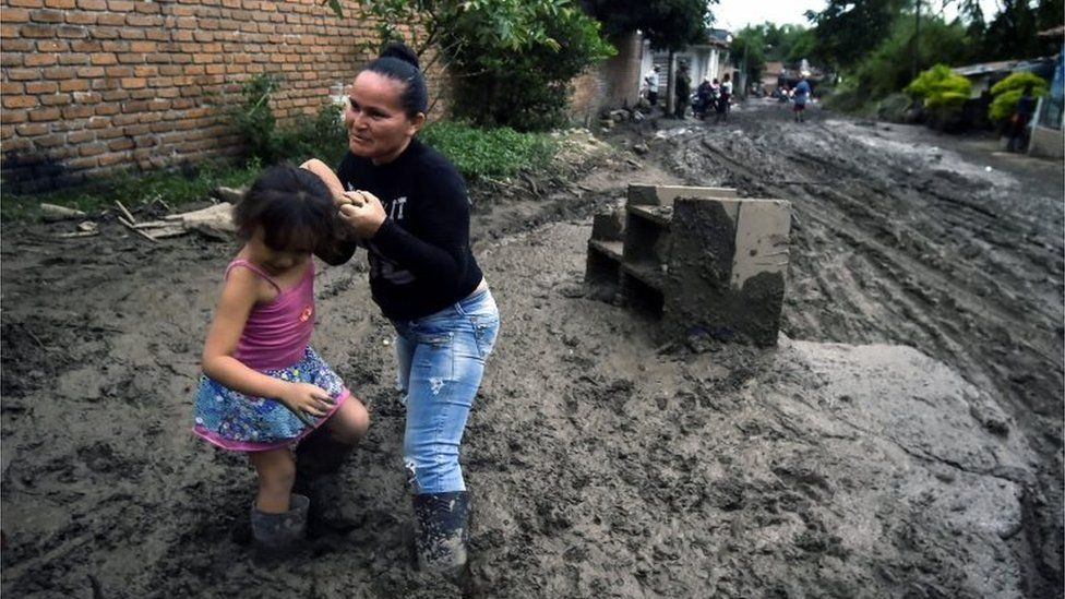 A woman and her daughter struggle to walk along a muddy street, after a mudslide due to heavy rains affected Corinto in Cauca department, southwest Colombia on November 8, 2017