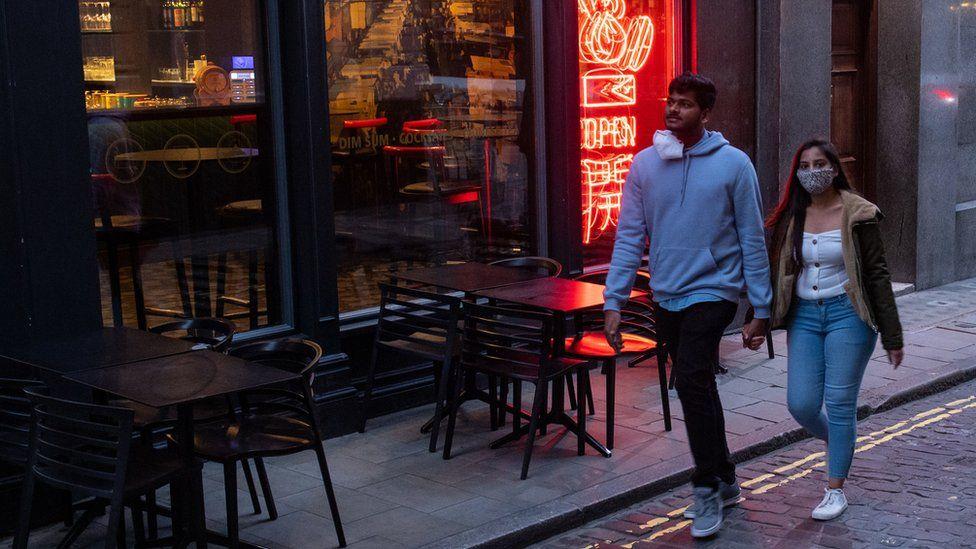 Couple walking past empty London restaurant
