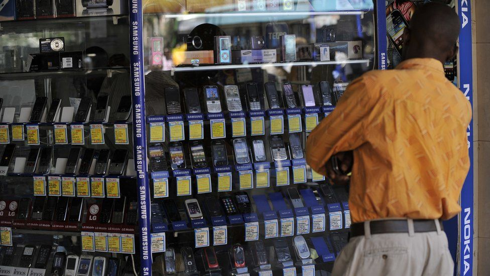 A man stands in front of a shop window displaying mobile phones on 1 October 2012 in Nairobi, Kenya.