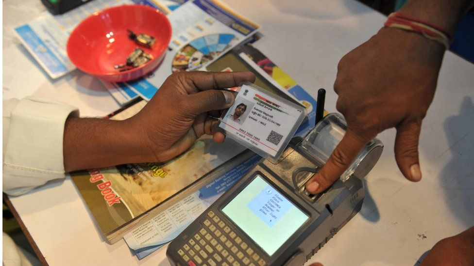 An Indian visitor gives a thumb impression to withdraw money from his bank account with his Aadhaar or Unique Identification (UID) card during a Digi Dhan Mela