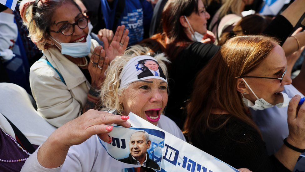 Supporters of Israeli Prime Minister Benjamin Netanyahu gather outside a court in Jerusalem where his corruption trial is taking place (5 April 2021)