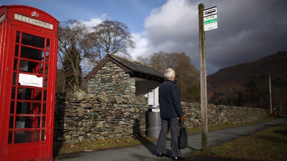 Woman waits at a rural bus stop