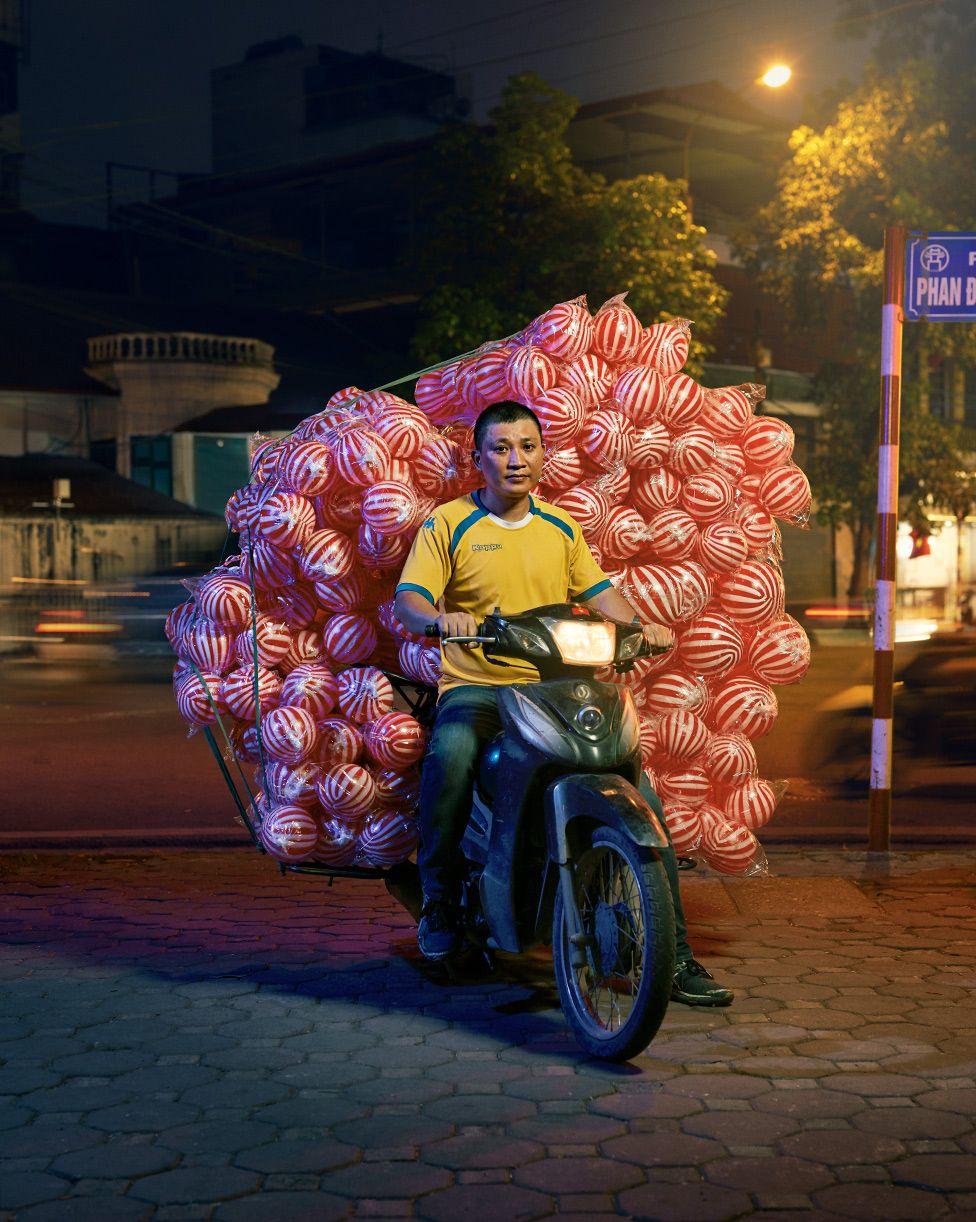 یہ شخص موٹر سائیکل پر سینکڑوں سرخ اور سفید رنگ کی گیندیں اٹھائے ہوئے ہے